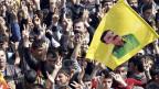 Kurdinnnen und Kurden skandieren Slogans und schwenken die Fahne mit dem Bild von PKK-Führer Abdullan Öcalan.
