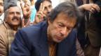 . Imran Khan (rechts, bei Essen) verspricht Jobs, Strom und Subventionen für die Bauern.
