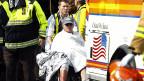 Ein verletzter Läufer im Rollstuhl, nach dem Bombenanschlag auf den Boston Marathon.