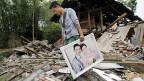 Ein Mann in der südwestchineischen Provinz Sichuan rettet ein Hochzeitsbild aus den Trümmern seines Hauses.