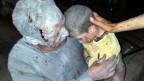 Ein verwundeter syrischer Mann hält seinen verletzten Sohn nach einem Luftangriff auf Saraqeb,Syrien. Die USA befürchten, dass chemische Waffen verwendet wurden.