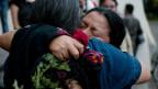Angehörige von Opfern umarmen sich nach dem Urteil