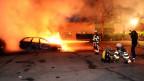 Feuerwehrmänner löschen ein brennendes Auto im Vorort Kista bei Stockholn, welches Jugendliche angezündet hatten.