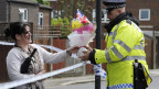 Eine Welt ohne Terrorismus habe es nie gegeben und es werde sie nie geben, meint der Anti-Terrorchef Mike Smith. Bild: Eine Frau überreicht einem Polizisten Blumen, dort wo 23. Mai ein Soldat brutal ermordet wurde.