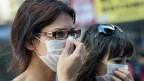 Türkische Frauen versuchen sich vor dem Tränengaseinsatz der Polizei zu schützen.