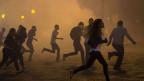 Die Demonstranten aus den Wolken von Tränengas während Anti-Regierungs-Proteste in Rio de Janeiro, Brasilien, Donnerstag, 20. Juni 2013.