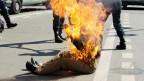 Ein Iraner liegt auf der Strasse in Paris, nachdem er sich selbst angezündet hat.