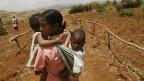 Eine afrikanische Frau trägt ihre Kinder nach Hause - nach stundenlangem Marsch nach dem Besuch in einer provisorischen Dorfklinik. In ihrem Dorf mangelt es an vielem: medizinische Versorgung. Schulen. Bildung. Es fehlt an Geld.