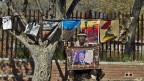 Ein Bewohner Sowetos posiert mit einem Footo von Nelson Mandela, am 1. Juli 2013.