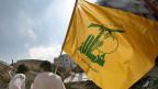 Zwei junge Männder mit einer Flagge der Hisbollah.