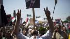 Ein Anhänger des gestürzten Präsidenten Ägyptens Mohammed Mursi macht das Victory-Zeichen, während er ein Banner auf dem Mund balanciert während einer Protestaktion in der Nähe der Universität von Kairo in Gizeh, Kairo, Ägypten, Freitag, 26. Juli 2013
