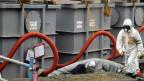 Ein Mitarbeiter in Schutzkleidung arbeitet rund um Tanks mit radioaktivem Wasser am AKW Fukushima am 12. Juni 2013. Über 300 000 Liter radioaktives Wasser sind ausgeflossen und versickern in Boden.