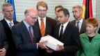 Der Ausschussvorsitzende Sebastian Edathy, (Mitte rechts) Parlamentspräsident Norbert Lammert (Mitte links) sowie andere Mitglieder des Ausschusses präsentieren den Abschlussbericht des Untersuchungsausschusses zur NSU in Berlin am 22. August 2013.