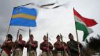 Ethnische Ungarn in traditionellen Uniformen mit der ungarischen und der Szekler-Flagge - in Rumänien.