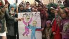 Proteste in einem syrischen Dorf bei Idlib. Die Karikatur sagt: «Russlands Putin sagt zu Syriens Assad: du kuschliger Volksmörder!»