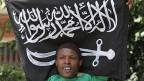 Ein junger Mann mit der Flagge der islamistischen al-Shabaab Milizen.