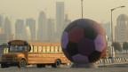 Ein überdimensionaler Fussball, der auf die Fussball-Weltmeisterschaft 2022 hinweist, in Doha im Emirat Katar. Die Gastarbeiter müssen unter menschenunwürdigen Zuständen arbeiten und werden ausgebeutet.