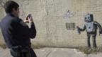 Ein Polizist fotografiert ein Graffiti des Künstlers Banksy.