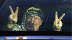 Der Palästinenser-Führer Yasser Arafat blickt aus seinem Auto und macht das Victory-Zeichen in der Stadt Ramallah im Februar 2002.