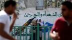 Jugendliche Palästinenser schlendern an einem Porträt von Netanyahu vorbe