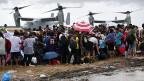 Menschen auf dem Flughafen Tacloban warten auf Evakuierung auf dem Luftweg; die Flugzeuge im Hintergrund kommen von einem Flugzeugträger der US-Marine.