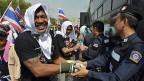 Händedruck zwischen Demonstranten, die gegen die Regierung protestieren und den Polizeikräften.