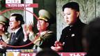 Nordkoreanische Fernseh-News: Rechts Kim Jong Un, im roten Kreis links sein Onkel Jang Song Thaek.