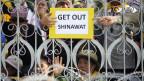 Anti-Regierungs-Demonstranten mit einem ein Plakat hinter einem Zaun am Regierungsgebäude in Bangkok am 9. Dezember 2013.