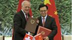 Beim Freihandelsabkommen mit China  konnte sich die Schweiz mit verbindlichen Menschenrechts-Standards durchsetzen. Bundesrat Schneider-Ammann am 6. Juli in Peking mit seinem Amtskollegen Geo Hucheng.