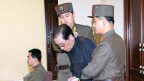 Chang Song Taek wird mit gefesselten Händen wird von zwei Uniformierten in den Gerichtssaal geführt.