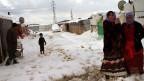 Syrische Flüchtlingsfrauen stehen vor ihrem Zelt in einem syrischen Flüchtlingslager in Al-Marj Dorf,  im libanesischen Bekaa-Tal östlich, am 10. Januar 2013.  Sie leiden nach einem heftigen Schneesturm unter Kälte und Nahrungsmittelknappheit .