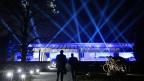 Ein Winterabend direkt am Genfersee. Blaue Scheinwerfer tauchen das neue Olympische Museum in ein entrücktes Licht. Musik rieselt, Wasserfontänen plätschern.