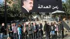 «Zeit für Gerechtigkeit» steht neben dem Portrait Rafik Hariris  auf der riesigen Werbetafel in Beirut. Darunter haben sich AnhängerInnen Rafik Hariris versammelt.