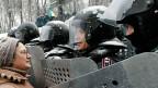Eine Demonstrantin spricht in Kiew mit Polizeikräften. In den letzten Stunden gab es Gewaltausbrüche - auf beiden Seiten.