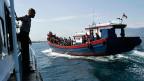 Indonesische Polizeikräfte bei einem Boot mit Flüchtlingen aus Burma; diese hoffen, die australische Küste zu erreichen.