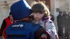 Ein Unicef-Mitglied evakuiert ein Kind aus der belagerten Altstadt von Homs im Zentrum von Syrien. Nun stoppt die Uno die Hilfsmission.