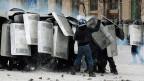 Einer der pro-europäischen Protestierenden attackiert in Kiew die Polizei.