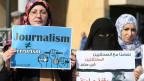 Demonstranten halten Schilder während einer Protestaktion gegen die Inhaftierung von Al Jazeera Journalisten in Ägypten, in der Innenstadt von Beirut am 8. Februar 2014.