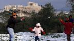 Weisse Woche: Antrieb für den Tourismus oder verlorene Unterrichtswoche? Bild: Eine Familie geniesst den Schnee vor der Akropolis.