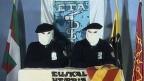 Zwei Mitglieder in Kapuzen der baskischen Untergrundorganisation ETA verlesen eine Erklärung für einen Waffenstillstand. Archivbild.