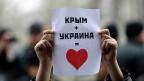«Die Krim + die Ukraine = ein Herz» steht auf dem Plakat einer Demonstrantin in Simferopol auf der Krim.
