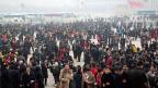 Delegierte der kommuniistischen Partei Chinas kommen für den Nationalen Volkskongress auf dem Tienanmen-Platz in Peking an - es herrscht dichter Smog.