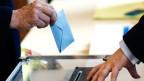 Ein Mann in Paris wirft seinen Wahlzettel ein
