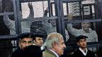Ein Anwalt von verhafteten Muslimbrüdern an einem Gericht in Kairo, im Hintergrund die Verhafteten in Käfigen, Dezember 2013.