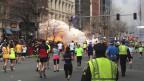 Bild vom Bostoner Marathon, im Vordergrund mehrere Läufer, im Hintergrund eine Explosion und Rauch.