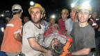 Grubenarbeiter transportieren einen verletzten Kumpel aus der Kohlenmine von Soma.
