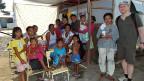 Am rechten Bildrand SRF-Reporter Tobias Fässler in Tacloban, neben ihm die Philippina Estrella mit Kindern, Enkeln und Nachbarn