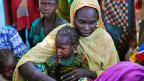 Eine Mutter und ihr Kind sitzen mit anderen Familien in einem Lager für Binnenvertriebene in der Nähe ihres Dorfes in Dougi, Kamerun, 24. Oktober 2013.