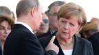 Der russische Präsident Wladimir Putin im Gespräch mit Bundeskanzlerin Angela Merkel am 6. Juni an der 70. D-Day Gedenkfeier in Ouistreham, Frankreich.