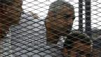 Die drei Al-Dschasira-Journalisten Peter Greste, Mohamed Fahmy Mohamed und Baher (L bis R) vor dem Gericht in Kairo am 23. Juni 2014.